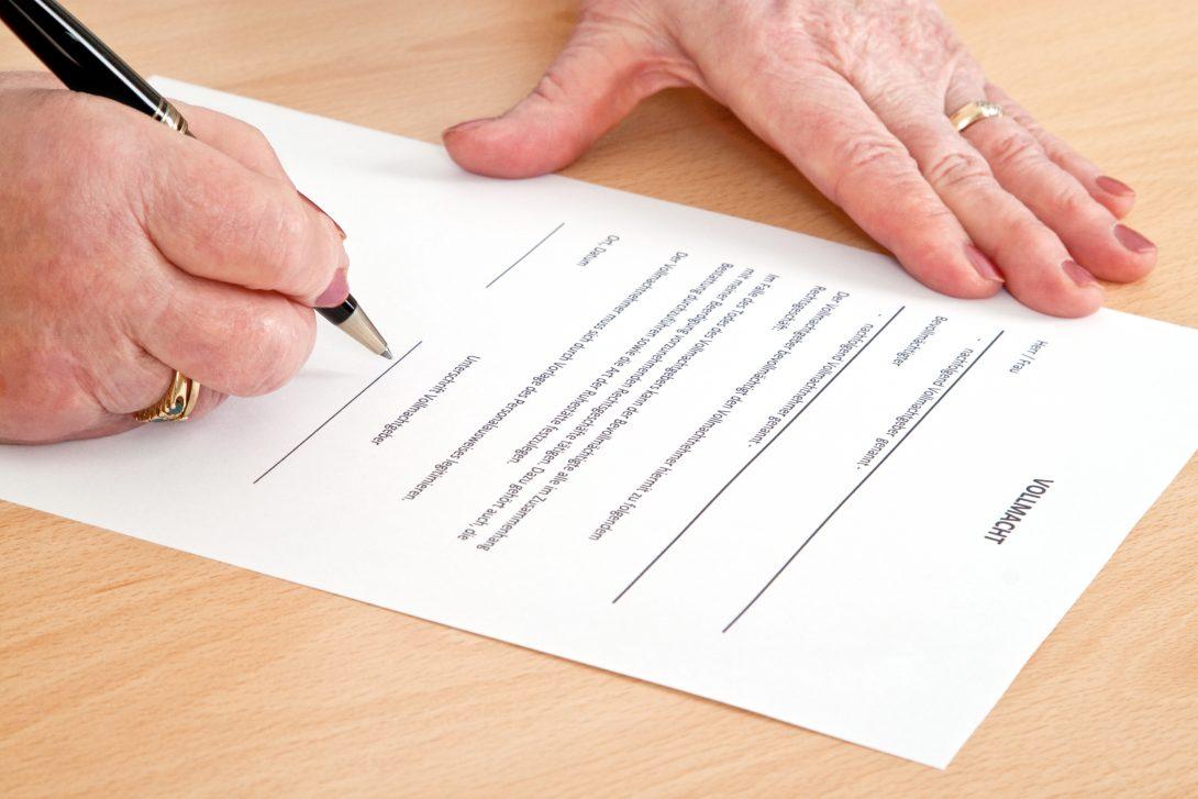 Alte Frau unterschreibt Vollmacht - Nahaufnahme