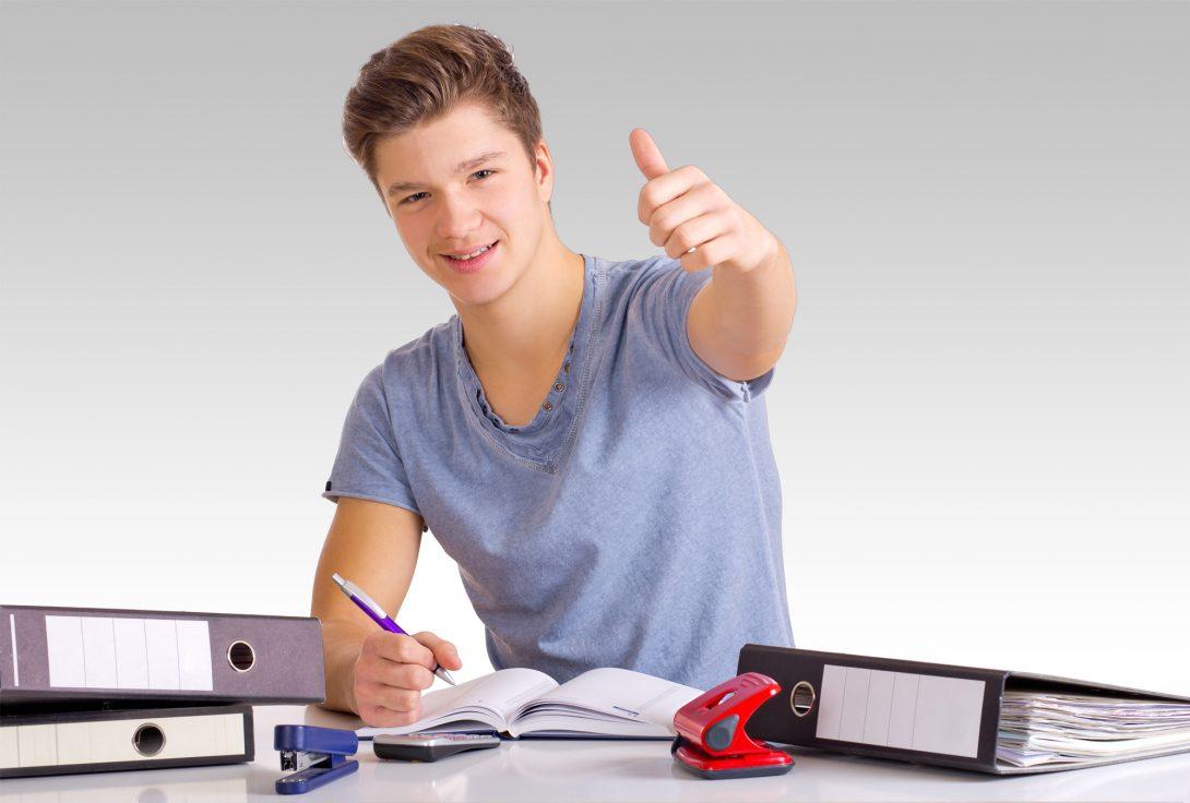 Lernender junger Mann sitzt an einem Schreibtisch