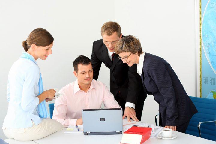 Vier Personen sitzen vor Laptop